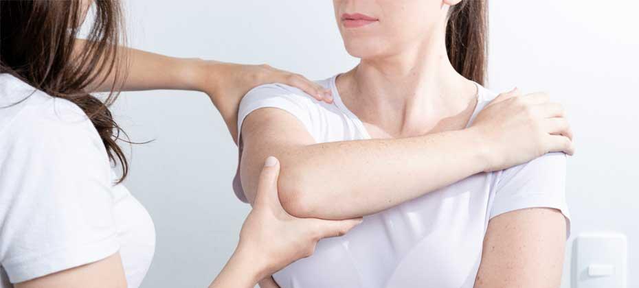 Woman bending patient arm over shoulder