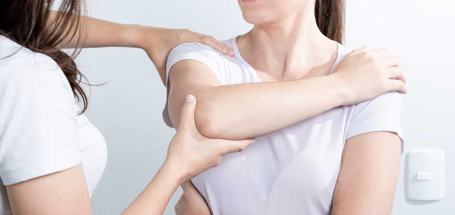 Physiotherapist assessing female patient arm movement