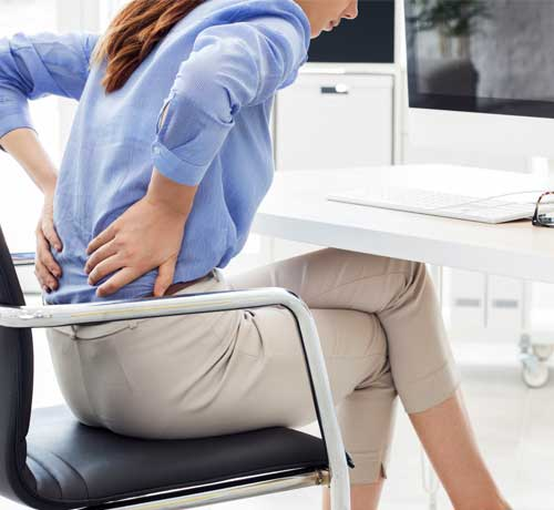 Woman sat at desk holding hands on lower back in pain
