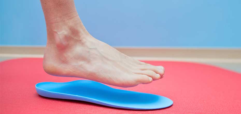 Foot hovering over blue orthotic foam mould