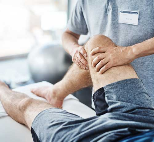 Male patient receives physiotherapy on knee