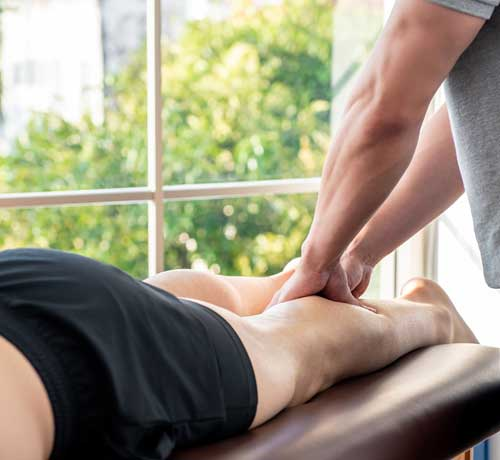 Person in sports clothes lying down having leg massaged by Physiotherapist