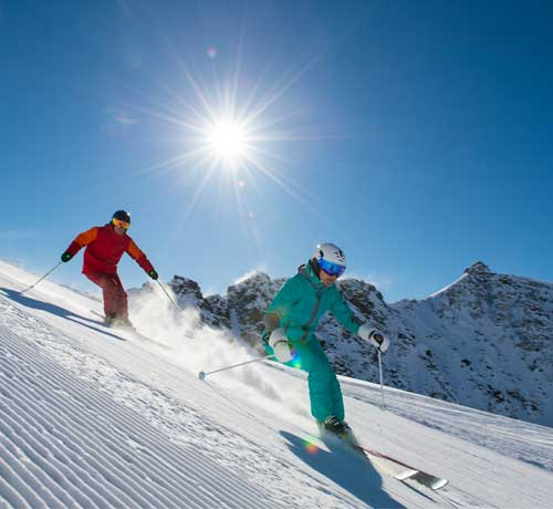 Two people skiing down a mountain with the sun shining